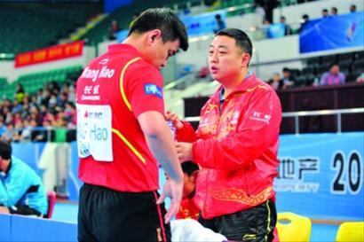 队参加2013乒乓球团体世界杯小组赛,刘国梁在比赛间隙和王皓交流
