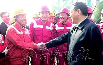 28日,总理与上海码头工人握手。
