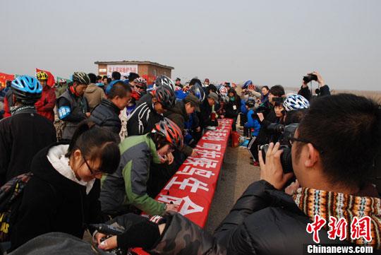 图为活动参与者在保护宣传条幅上签名支持保护候鸟。中新社发 刘权喜 摄