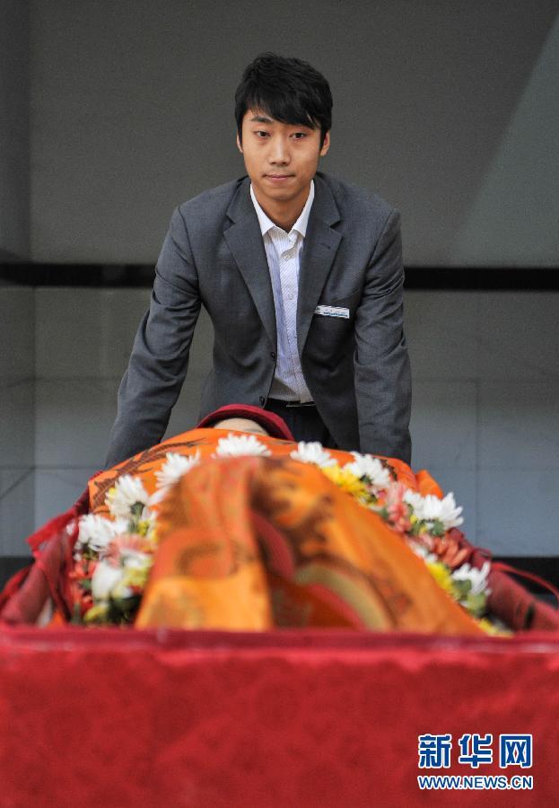 4月2日,火化工刘洋将一具遗体推向火化炉.