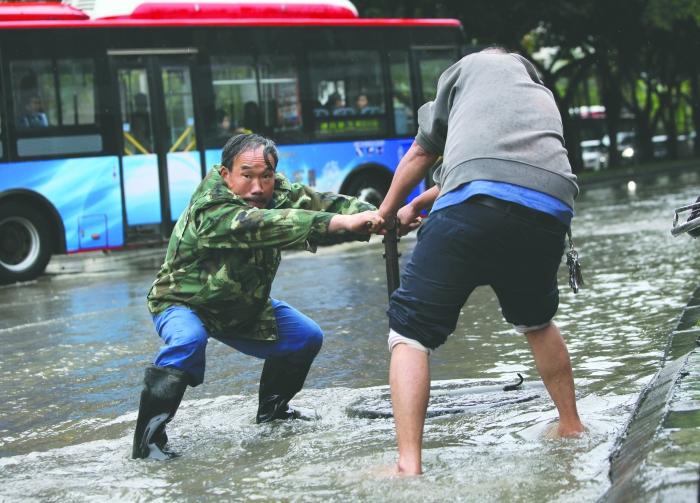 大石西路上两位自来水公司工作人员正在打开排水阀 摄影记者 鲍泰良