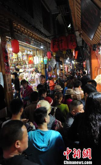 """4月5日晚,湖南凤凰古城内的街道被游客""""堵""""得水泄不通,众多游客纷纷选择清明前往凤凰游玩。杨华峰 摄"""