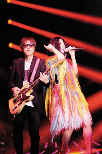 《我是歌手》音乐总监梁翘柏(左)与歌手尚雯婕(右)同台演出。