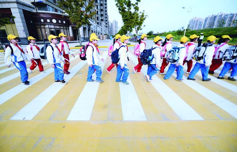 4月8日,九江开发区鹤湖小学三年级学生通过爱心斑马线.