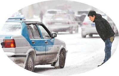 """大雪天,冰城哈尔滨市民打车变得更加艰难,能""""拼车""""出行就算幸运。图为准备""""拼车""""的市民在询问司机是否顺路。"""