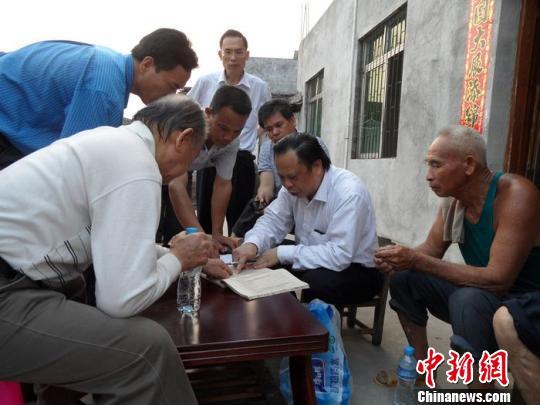 图为玉林市侨联主席钟雄右二正在核对庞氏族谱。