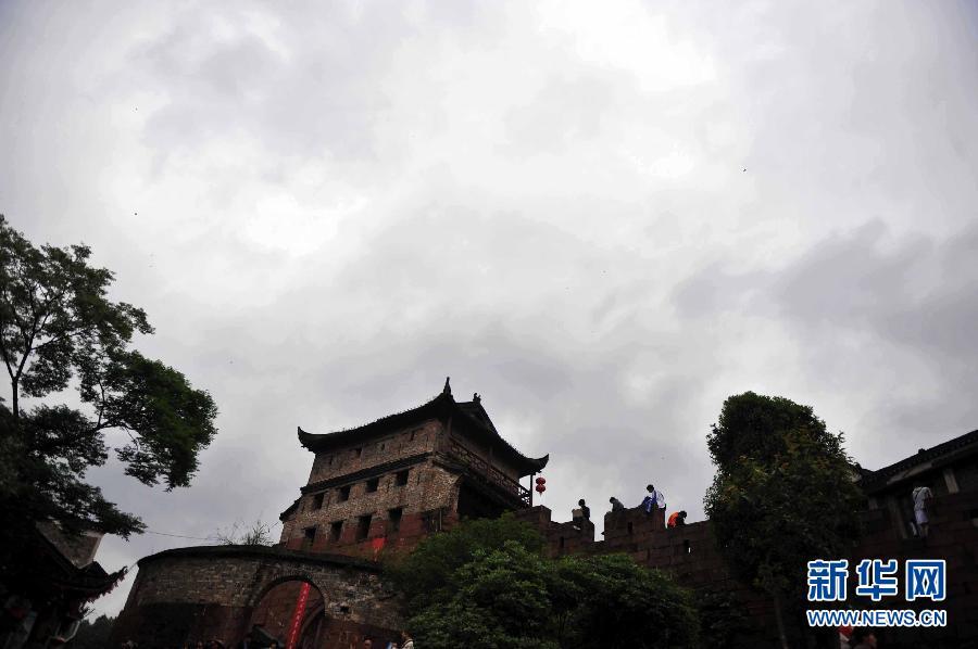 4月10日,一名导游在凤凰古城一处售票点购买门票。