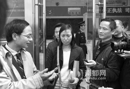昨日,唐慧(中)与代理律师斯伟江(左)接受媒体采访。 中新社发