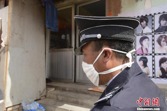 """4月13日,位于北京市顺义区后沙峪镇古城村的一户居民家被戴口罩的保安""""封锁"""",禁止闲人靠近。这户人家的一名7岁小女孩被确诊为北京市首例H7N9禽流感病例。中新社发 侯宇 摄"""