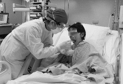 北京地坛医院工作人员在ICU病房给小圆圆喂饭 摄/新华社