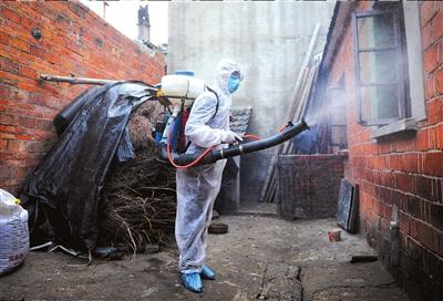 一位防疫人员对H7N9禽流感患者的鸡舍进行消毒。新华社发