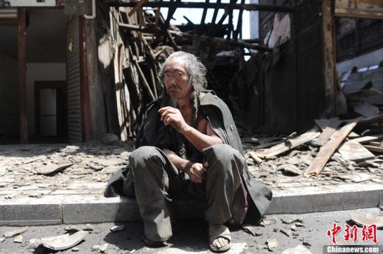 4月20日,四川雅安芦山发生7.0级地震,一位当地民众在震后路边避险。中新社发 张浪 摄