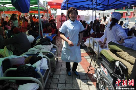 4月20日,四川雅安芦山发生7.0级地震后,雅安荥经县部分伤员和医院大楼的患者被转移到了临时的救治点接受治疗。中新社发 张浪 摄