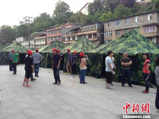 """4月20日18时,四川雅安市地震灾区,雅安市人民医院在户外撑起""""帐篷医院"""",大量伤员及其家属被安置在帐篷下。图为""""帐篷医院""""下。 陈曦 摄"""