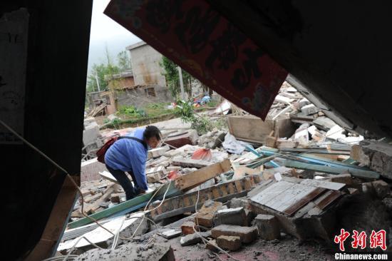 4月20日,四川雅安芦山7.0级地震发生后,芦山大地满目疮痍,灾区民众失去家园。图为灾区民众在完全坍塌的房屋上搜寻物品。中新社发 张浪 摄