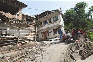 4月20日,四川省雅安市芦山县地震重灾区龙门乡的受灾居民在因地震受损的房屋外休息 新华社发