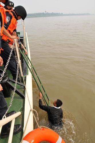 4月21日,联合巡逻执法船艇编队船员在救助落水群众。当日,第九次湄公河联合巡逻执法船艇编队在金三角上浅滩附近水域成功救助一艘老挝籍遇险渔船和2名老挝籍落水群众。新华社记者 李萌 摄