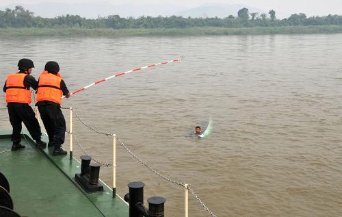 4月21日,联合巡逻执法船艇编队船员在救助落水群众。新华社记者 李萌 摄