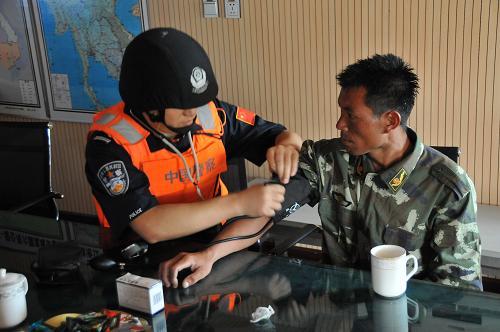 4月21日,联合巡逻执法船艇编队船员为获救的群众检查身体。新华社记者 李萌 摄