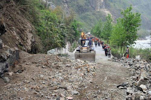 月21日,在通往宝兴县的210省道上,一台大型推土机在清理公路路面上的碎石堆。新华社社记者刘潺摄