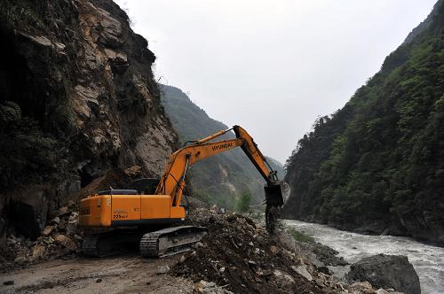 4月21日,在通往宝兴县的210省道上,一台大型挖掘机在清理公路路面上的碎石堆。新华社社记者刘潺摄