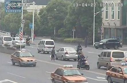 今天上午10:21,长江广场前的全球眼清晰的显示,天元大桥桥头一位中年妇女提着东西不顾安危在急行的车辆内穿梭,一辆灰色的小车在她身边擦过,她却仍然前行。