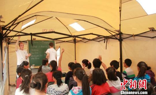 """西南财大的志愿者在""""帐篷学校""""里给孩子们上课 李卢 摄"""