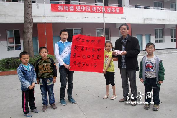 北方网雅安特派记者辛华水把中央党校第十三期中青二班四支部老师和31名学员的捐款亲手交到芦阳小学校长徐宏手中。