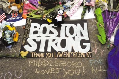 """4月21日,写有波士顿连环爆炸案遇难者名字、""""波士顿强大""""以及""""谢谢执法部门""""的悼念物品搁置在事发地附近的一处地点。"""