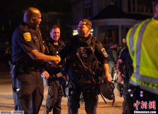 美国警方19日表示,他们已经抓获在逃的波士顿爆炸案嫌疑人焦哈尔・萨纳耶夫。此前,警方在波士顿展开全城搜捕,并将嫌犯围困在沃特敦一座建筑内。图为警官在嫌疑人被捕地点握手庆祝。