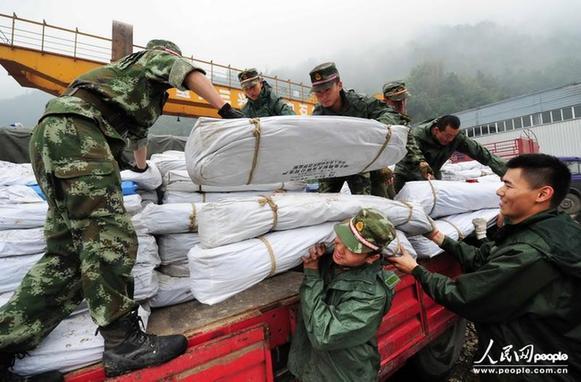 在四川省宝兴县灵关镇救灾物资集中点,武警四川总队南充支队的官兵在搬运救灾帐篷。