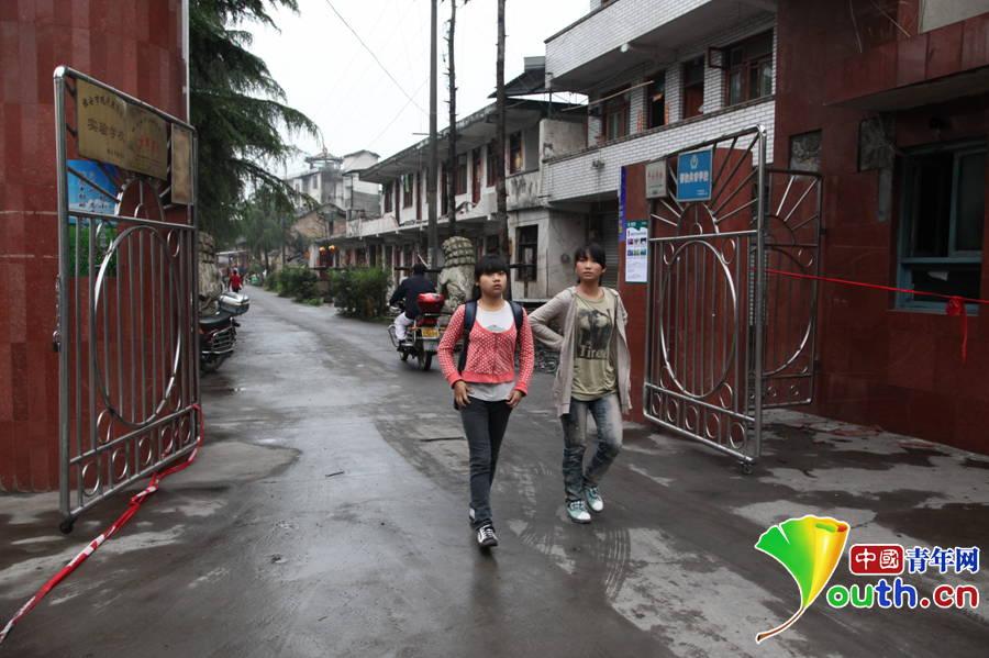 地震发生后的第四天,国张9年级5班的罗萍、骆玉琴走进校门,回校复课。