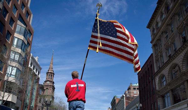 2013年4月22日,美国波士顿,一名消防队员在默哀仪式后在马拉松终点处举起了美国国旗。   本报记者 马欢 发自广州   2013年4月15日,波士顿马拉松终点处,街道两边人头攒动,两颗炸弹突然在观众中爆炸无数目击者讲述了当时惊心动魄的一幕。   人群迅速被疏散,爆炸现场立刻封锁,伤者被1分钟内抵达现场的救护车送院急救。   四天后,为搜捕嫌疑犯,波士顿发布了安全专家称为史无前例的居民禁止外出令。在搜捕中心地区沃特顿,士兵、特警队、直升机和全副武装的装甲车封锁了大片街区在旁观者看来,这样的场