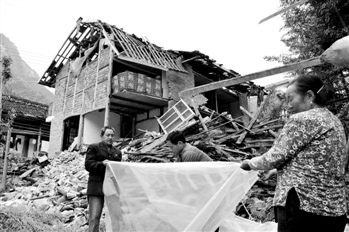宝盛乡凤头村的灾民在坍塌的房子旁边搭帐篷 本报记者 纪粤鸣 摄