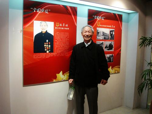 89岁的全国劳模陈荣材在介绍自己的展板前拍照留念图片