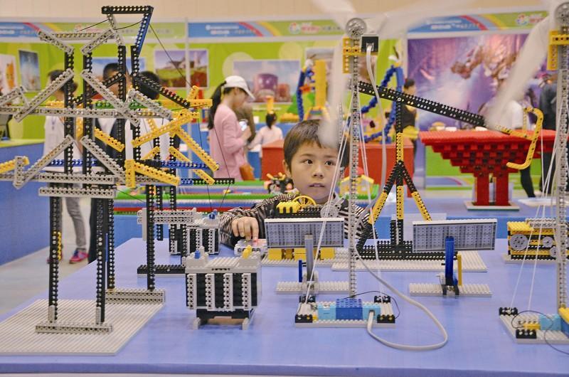 """青少年科技节上,一名小学生被""""慧学慧玩""""展区的创意科技手工作品吸引.图片"""