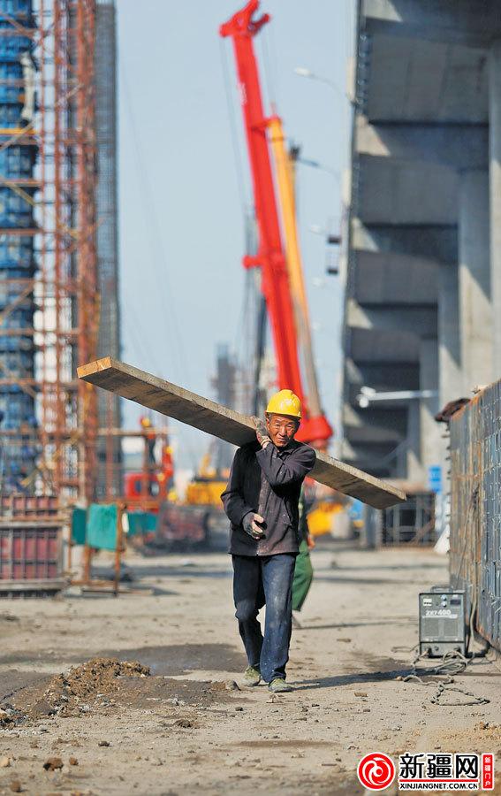 """在"""" 田""""字型快速路二期克西路立交(bk标段),一名建筑工人正在搬运木材"""