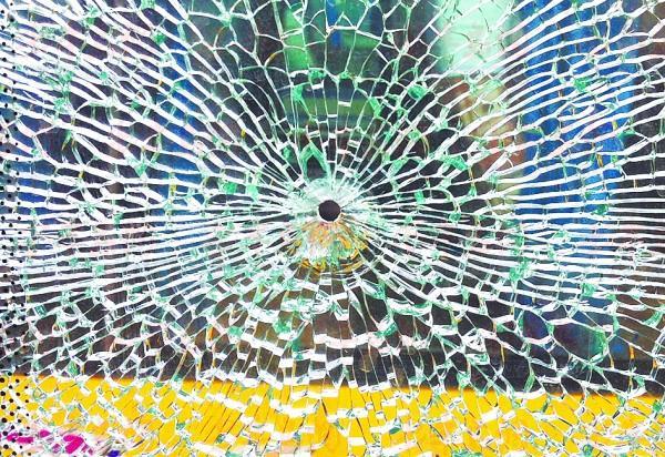 其中一辆客车的车窗被击中后呈蜘蛛网状.高清图片
