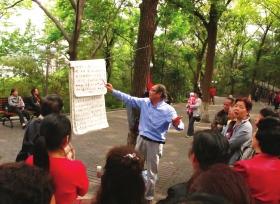 4月11日,重庆北碚公园,一名老人在教唱一首红歌。2012年4月以后,红歌潮瞬然消退,只剩下一些老人在广场、公园坚持,以充实晚年生活。图/记者倪志刚