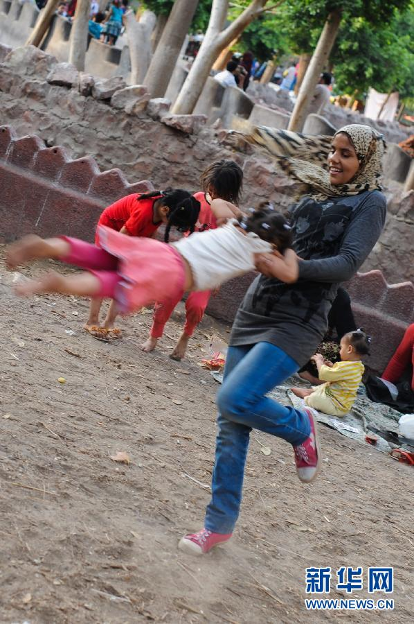 5月6日,在埃及开罗的吉萨动物园,一名妇女在和孩子玩耍.