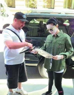 范冰冰敷着面膜帮老外粉丝签名。