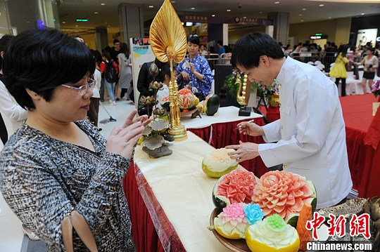 杨华峰 长沙/一位泰国厨师在现场表演水果雕花。杨华峰摄