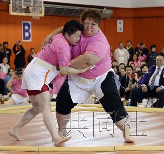 """5月12日下午,北海道福岛举办""""女子相扑大会""""。图为艺名为""""肥山""""的山本静香在决赛中击败去年冠军""""悦乃海""""(左)。共同社"""