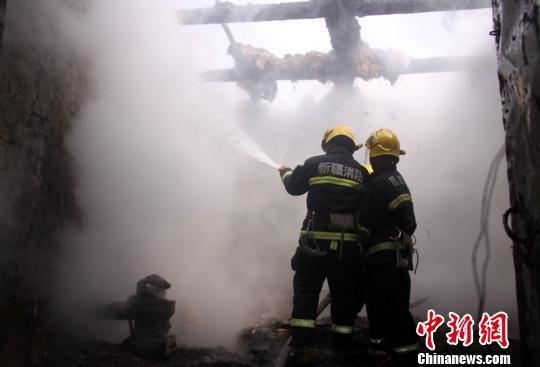 图为新疆昌吉州玛纳斯县消防人员正用水枪灭火。 洪文乐 摄