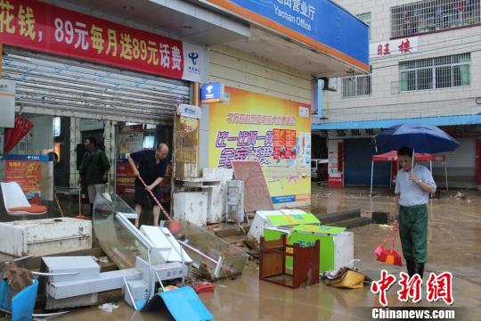 灾民清扫洪水带来的淤泥 黄小广 摄