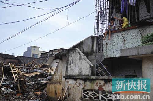 暴雨过后的佛冈县水头镇,两个孩子坐在二楼的防盗网上玩耍,不远处,是一所在洪水中被冲塌的房子。