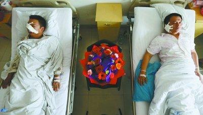 身受重伤的两位民警在医院接受治疗,战友们送上康乃馨祝福他们早日康复。