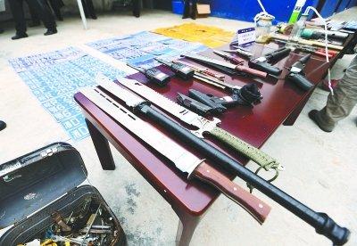 麻城市公安局缴获的犯罪团伙使用的各种管制刀具、钢叉及自制手枪等作案工具以及涉案的大量车牌。