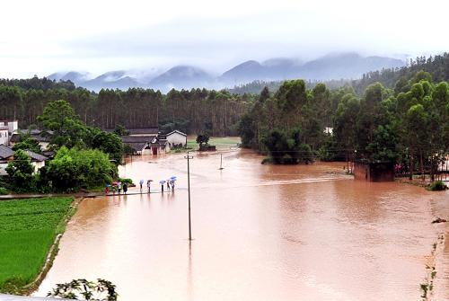 5月19日,广东省梅州市蕉岭县文福镇的农田和道路被洪水淹没。 新华社发(钟小丰 摄)