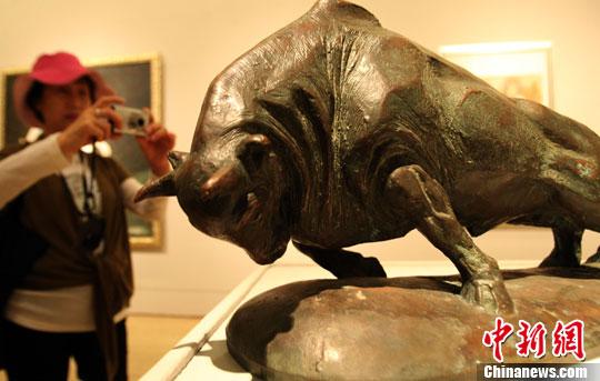 """5月20日,""""与时代同行中国美术馆50年馆藏作品大展""""在北京拉开帷幕。图为展览作品吸引参观者。中新社发 钱兴强 摄"""